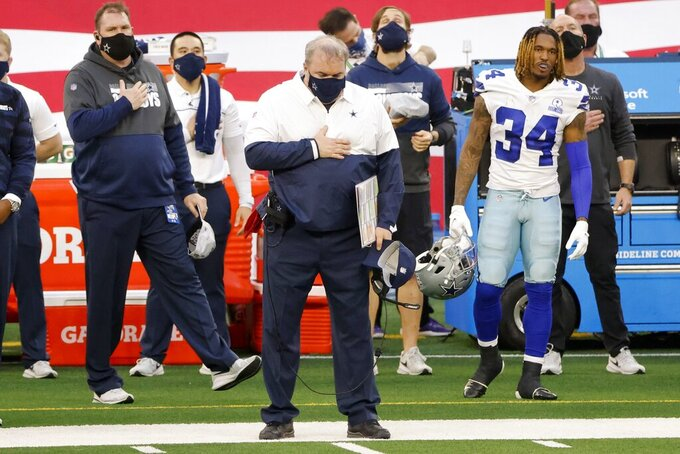 Dallas Cowboys head coach Mike McCarthy stands by running back Rico Dowdle (34) during the playing of the national anthem before the start of the first half of an NFL football game against the Philadelphia Eagles in Arlington, Texas, Sunday, Dec. 27. 2020. (AP Photo/Michael Ainsworth)