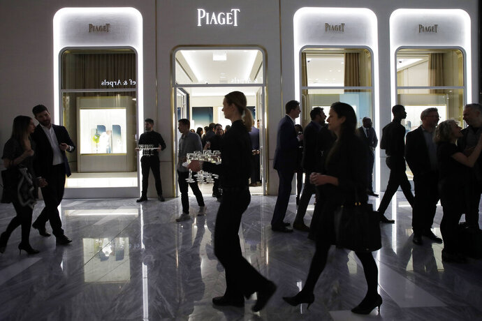 FILE- In this March 14, 2019, file photo people attend the opening of a Piaget store during the opening night of The Shops & Restaurants at Hudson Yards in New York. The U.S. job market isn't quite as strong as originally believed, with revised figures showing that the economy had 501,000 fewer total jobs this March than initially reported. The Labor Department says that nearly two-thirds of the downward revision came from the retail and leisure and hospitality sectors, the industries most associated with consumer spending.  (AP Photo/Mark Lennihan, File)