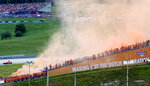 Fans set off orange smoke flares as they arrive to cheer on Red Bull driver Max Verstappen of the Netherlands during the Austrian Formula One Grand Prix at the Red Bull Ring racetrack in Spielberg, Austria, Sunday, July 4, 2021. (AP Photo/Darko Bandic)