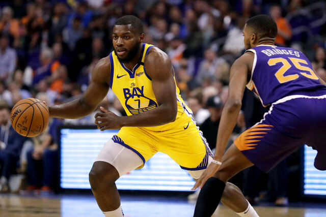 Golden State Warriors forward Eric Paschall (7) drives past Phoenix Suns forward Mikal Bridges (25) during the first half of an NBA basketball game Saturday, Feb. 29, 2020, in Phoenix. (AP Photo/Matt York)
