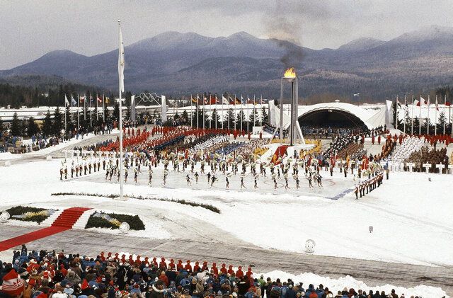 FILE - This Feb. 13, 1980, file photo shows the opening ceremony of the XIII Winter Olympics in Lake Placid, N.Y. Lake Placid is celebrating the 40th anniversary of the Winter Olympics that were held in the Adirondack Mountain village. It's an important moment for Lake Placid, which will host the 2023 Winter World University Games, and a reminder of its place as one of only three resort towns to host two Winter Olympiads.(AP Photo)