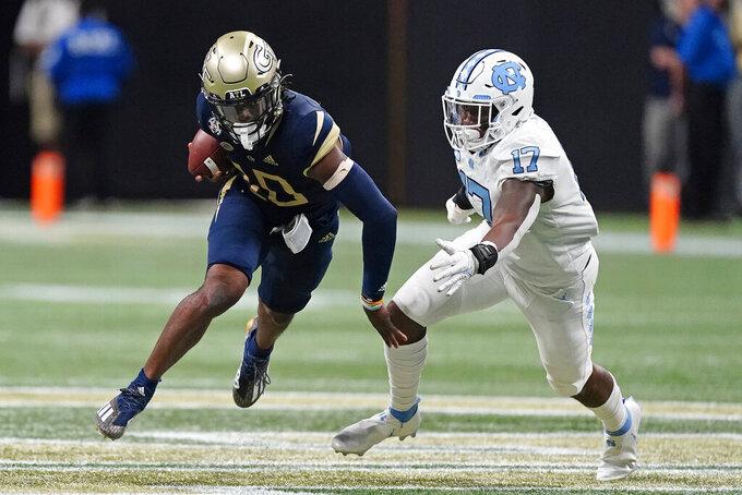 Georgia Tech quarterback Jeff Sims (10) gets past North Carolina linebacker Chris Collins (17) during the second half of an NCAA college football game, Saturday, Sept. 25, 2021, in Atlanta. (AP Photo/John Bazemore)