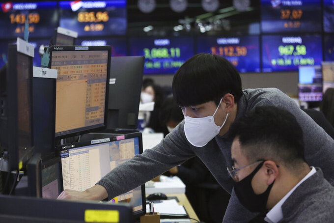 Currency traders watch monitors at the foreign exchange dealing room of the KEB Hana Bank headquarters in Seoul, South Korea, Thursday, Jan. 28, 2021. Asian shares skidded on Thursday as a reality check set in about longtime economic damage from the coronavirus pandemic, giving Wall Street its worst day since October.(AP Photo/Ahn Young-joon)