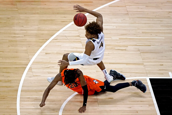 West Virginia's Miles McBride (4) trips over Oklahoma State's Keylan Boone (20) during the first half of an NCAA college basketball game in the second round of the Big 12 Conference tournament in Kansas City, Mo., Thursday, March 11, 2021. (AP Photo/Charlie Riedel)