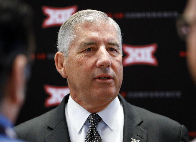 """FILE - In this July 15, 2019, file photo, conference commissioner Bob Bowlsby answers questions from reporters after his opening remarks on the first day of Big 12 Conference NCAA college football media days, at AT&T Stadium in Arlington, Texas. Parity in the Big 12 this season makes for good competition but also presents a quandary about the league's chances of qualifying a team for the College Football Playoff. Bowlsby says parity """"makes it more difficult, there isn't any question about that.""""(AP Photo/David Kent, File)"""