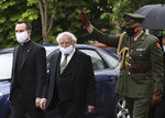 The President of Ireland Michael D Higgins, center, arrives to attend former Northern Ireland lawmaker and Nobel Peace Prize winner John Hume's funeral Mass at St Eugene's Cathedral in Londonderry, Northern Ireland, Wednesday, Aug. 5, 2020. Hume was co-recipient of the 1998 Nobel Peace Prize with fellow Northern Ireland lawmaker David Trimble, for his work in the Peace Process in Northern Ireland. Higgins is wearing a mask due ti the ongoing outbreak of the Coronavirus. (AP Photo/Peter Morrison)