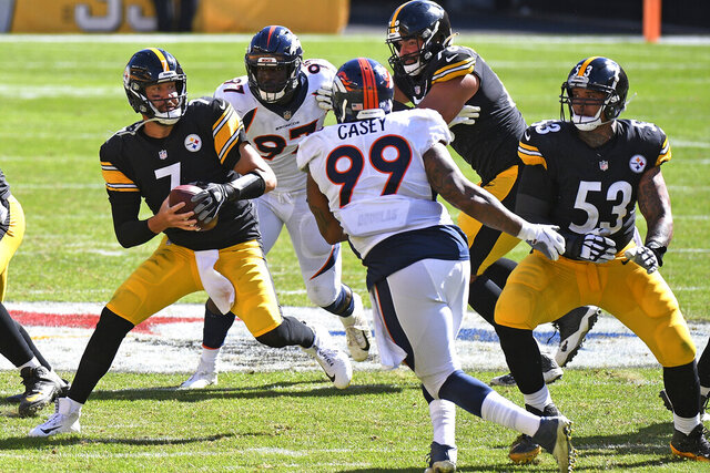 Pittsburgh Steelers quarterback Ben Roethlisberger (7) moves out of the pocket under pressure from Denver Broncos defensive end Jurrell Casey (99) and linebacker Jeremiah Attaochu (97) during the second half of an NFL football game in Pittsburgh, Sunday, Sept. 20, 2020. (AP Photo/Don Wright)