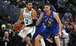 Boston Celtics forward Jayson Tatum, left, looks to pass the ball as Denver Nuggets forward Juan Hernangomez defends during the first half of an NBA basketball game Friday, Nov. 22, 2019, in Denver. (AP Photo/David Zalubowski)