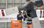 Aircraft Mechanic Cody Poole inspect one of the engines on a recently acquired C-130 aircraft, that will be used for firefighting, hangared at the California Department of Forestry and Fire Protection's Sacramento Aviation Management Unit based at McClellan Airpark in Sacramento, Calif., Friday, July 23, 2021. Firefighters are trying to become smarter in how they prepare for the drought- and wind-driven wildfires that have become more dangerous across the American West in recent years, including by adding aircraft like the Sikorsky Firehawk helicopters or military surplus C-130 transport aircraft retrofitted to drop fire retardant. (AP Photo/Rich Pedroncelli)