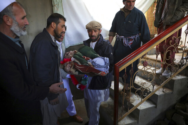 Relatives carry the dead body of a boy who was killed by a mortar shell attack in Kabul, Afghanistan, Saturday, Nov. 21, 2020. Mortar shells slammed into different parts of the Afghan capital on Saturday. (AP Photo/Rahmat Gul)