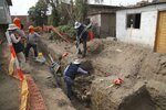 In this Feb. 12, 2020 photo, archaeologists and gas workers stand at the site where ancient bones and vessels from a previous Inca culture were discovered during the digging of a new natural gas line through the Puente Piedra neighborhood of Lima, Peru. About 300 archaeological finds, some 2,000 years old, have been reported over the past decade during the building of thousands of kilometers (miles) of natural gas pipelines in the capital. (AP Photo/Martin Mejia)