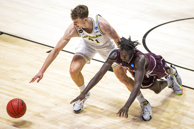 Michigan's Franz Wagner (21) and Texas Southern's Yahuza Rasas compete for a loose ball during the second half of a first-round game in the NCAA men's college basketball tournament, Saturday, March 20, 2021, at Mackey Arena in West Lafayette, Ind. (AP Photo/Robert Franklin)