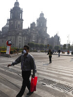 A man wearing a face mask crosses a street by the Metropolitan Cathedral, shrouded by haze, in the Zocalo, Mexico City's main square, Thursday, May 16, 2019. A siege of air pollution blanketing the capital has led to school closures and the cancellation of professional sporting events. (AP Photo/Rebecca Blackwell)