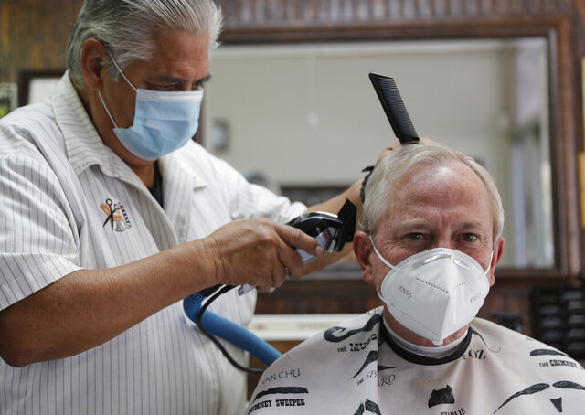 Barber Rudy Soliz gives Brian Barnett a haircut at the San Marcos Barber Shop in San Marcos, Texas, Thursday, May 21, 2020. Businesses in Texas closed due to the COVID-19 pandemic continue to open in phases; bars are permitted to open Friday. (AP Photo/Eric Gay)