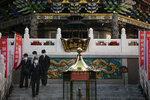 In this Feb. 13, 2020, photo, a group of people in school uniforms walk down the steps of a temple in Yokohama's Chinatown, near Tokyo. A top Olympic official made clear Friday the 2020 Games in Tokyo will not be cancelled despite the virus that has spread from China. (AP Photo/Jae C. Hong)