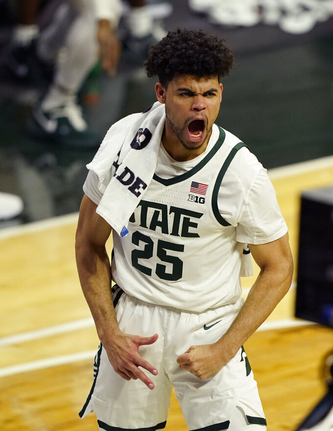Michigan State forward Malik Hall reacts after a teammate's three-point basket during the first half of an NCAA college basketball game against Michigan, Sunday, March 7, 2021, in East Lansing, Mich. (AP Photo/Carlos Osorio)