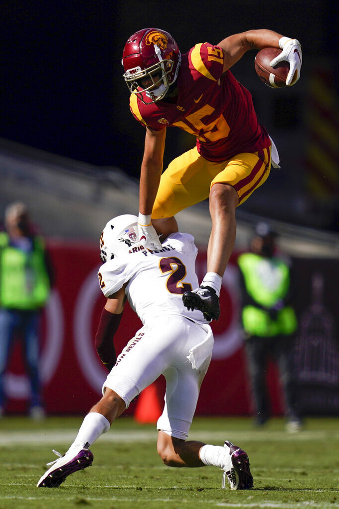 Southern California wide receiver Drake London (15) hurdles over Arizona State defensive back DeAndre Pierce (2) during the first half of an NCAA college football game Saturday, Nov. 7, 2020, in Los Angeles. (AP Photo/Ashley Landis)