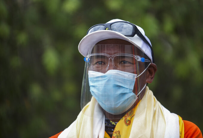 Veteran Sherpa guide Kami Rita who returned  from the mountains on a helicopter arrives at the airport in Kathmandu, Nepal, Tuesday, May 25, 2021. The record-holding Sherpa climber halted his attempt to scale Mount Everest for a 26th time because of a bad dream but plans to try again next year. (AP Photos/Bikram Rai)