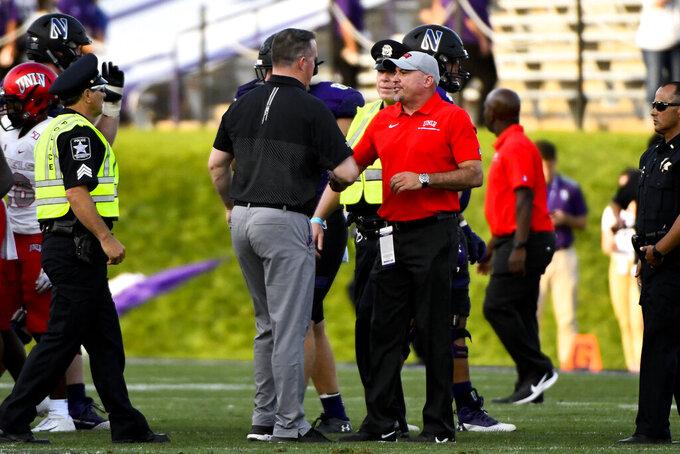 Northwestern head coach Pat Fitzgerald, center left, and UNLV head coach Troy Sanchez shake hands after an NCAA college football game, Saturday, Sept. 14, 2019, in Evanston, Ill. Northwestern won 30-14. (AP Photo/Matt Marton)