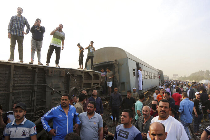 People gather at the site where a passenger train derailed injuring at least 100 people, in Banha, Qalyubia province, Egypt, Sunday, April 18, 2021. At least eight train wagons ran off the railway, the provincial governor's office said in a statement. (AP Photo/Fadel Dawood)