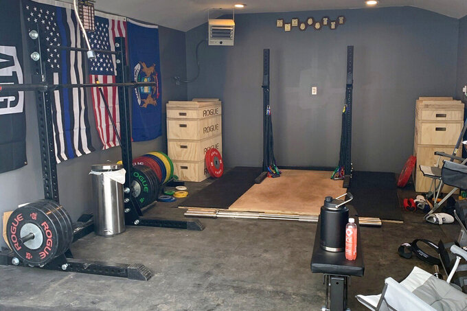 This May 7, 2020, image provided by weightlifter Kate Nye, shows her garage gym at her home in Berkley, Mich. The coronavirus crisis has forced many athletes to be creative as they try to continue their training, but in some Olympic sports, working from home is fairly routine. Nye trains in her garage. (Kate Nye via AP)