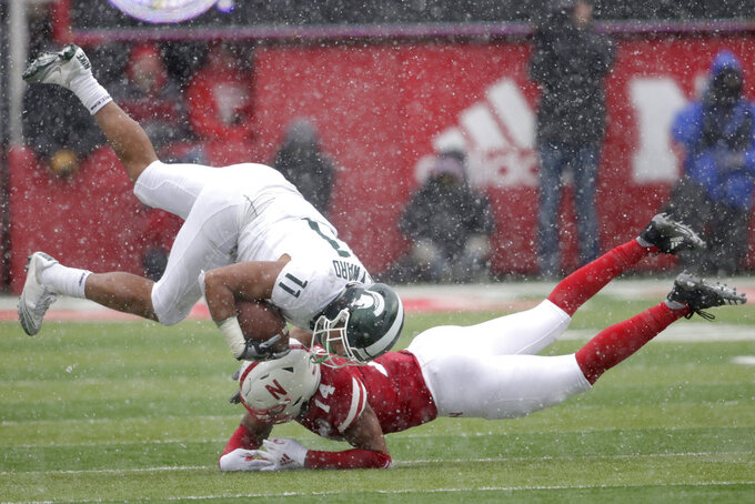 Nebraska defensive back Tre Neal (14) upends Michigan State running back Connor Heyward (11) after he made a catch during the second half of an NCAA college football game in Lincoln, Neb., Saturday, Nov. 17, 2018. Nebraska won 9-6. (AP Photo/Nati Harnik)