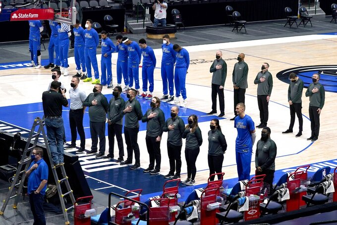 Dallas Mavericks players and staff stand during the playing of the national anthem before the first half of an NBA basketball game against the Atlanta Hawks in Dallas, Wednesday, Feb. 10, 2021. (AP Photo/Tony Gutierrez)