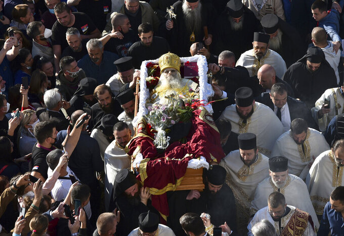 Believers carry coffin of Bishop Amfilohije, the head of the Serbian Orthodox Church in Montenegro, in Podgorica, Montenegro, Saturday, Oct. 31, 2020. The church said the 82-year-old died Friday from pneumonia caused by COVID-19. Amfilohije, known for his staunch anti-Western and pro-Russian political views, played a key role in leading the anti-government protests and putting together an opposition coalition that is currently trying to form the country's new government. (AP Photo/Risto Bozovic)