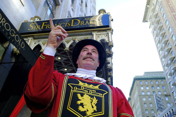 In this photo taken Monday, Jan. 6, 2020, Beefeater doorman Tom Sweeney points up Powell Street while standing outside the Sir Francis Drake Hotel in San Francisco. Sweeney has opened doors for movie stars and shaken hands with every U.S. president since Gerald Ford, with the exception of Donald Trump. He's taken photos with countless visitors from around the world, often after telling them where to catch the cable car and how to get to Fisherman's Wharf. The man known as a