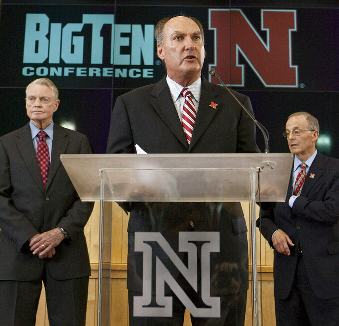 FILE - This June 11, 2010, file photo shows Big Ten commissioner Jim Delany, center, speaking about Nebraska leaving the Big 12 to join the Big Ten during a press conference in Lincoln, Neb., with Nebraska's athletic director Tom Osborne, left, and Nebraska Chancellor Harvey Perlman, right. Delany, one of the most influential figures in college athletics for three decades, will step down as Big Ten commissioner when his contract expires June 30, 2020. The Big Ten announced Delany's plans on Monday, March 4, 2019. The 71-year-old has been commissioner since 1989.  (AP Photo/Nati Harnik, File)