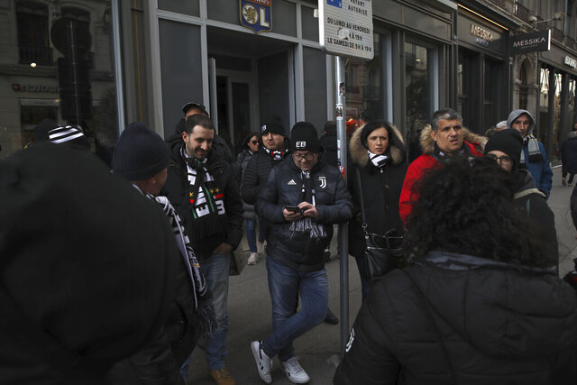 Juventus supporters tour Lyon, central France, ahead of the Champions League , round of 16th, first leg match Lyon against Juventus, Wednesday Feb. 26, 2020. Up to 3,000 Juventus fans are expected. As the coronavirus cases clustered in northern Italy kept climbing and European countries reported new ones with Italian travel ties Tuesday, authorities across the continent tried to strike a balance between taking prudent public health measures and preventing panic. (AP Photo/Daniel Cole)