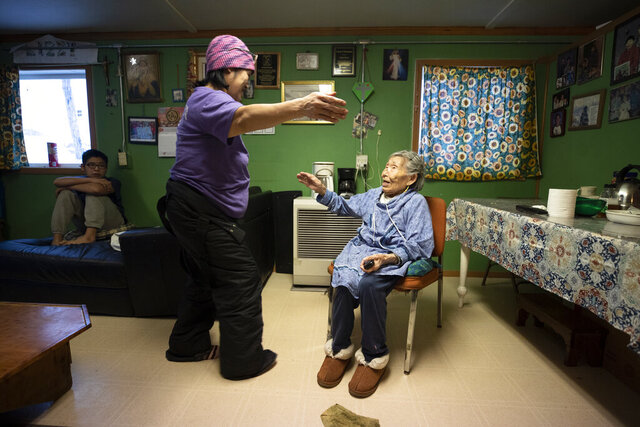 In this Monday, Jan. 20, 2020 image, Lizzie Chimiugak, right, gets a hug from her granddaughter Janet Lawrence at her home in Toksook Bay, Alaska. Chimiugak, who turned 90 years old on Monday, is scheduled to be the first person counted in the 2020 U.S. Census on Tuesday. (AP Photo/Gregory Bull)