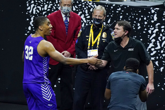 Abilene Christian head coach Joe Golding shakes hands with Joe Pleasant (32) as they leave the court after Abilene Christian upset Texas in a college basketball game in the first round of the NCAA tournament at Lucas Oil Stadium in Indianapolis Sunday, March 21, 2021. Pleasant made two decisive free throws as Abilene Christian beat Texas 53-52. (AP Photo/Mark Humphrey)