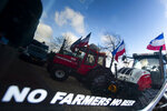 Tractors are reflected in a car window during a farmers demonstration in The Hague, Netherlands, Wednesday, Feb. 19, 2020. Dutch farmers, some driving tractors, poured into The Hague on Wednesday to protest government moves to rein in carbon and nitrogen emissions to better fight climate change. (AP Photo/Peter Dejong)