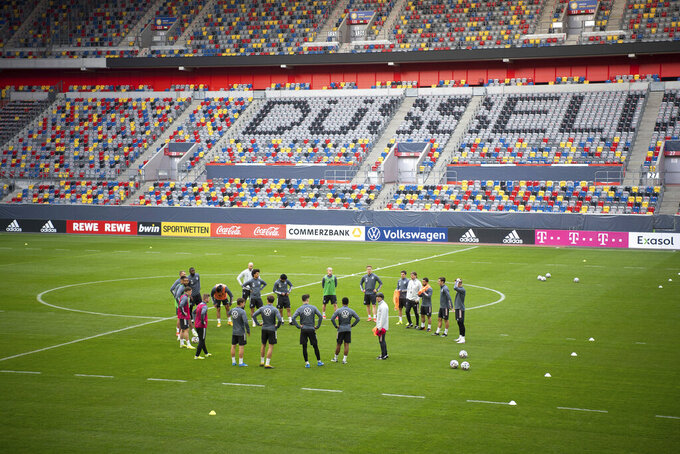 German national soccer team players stand in an empty stadium during a team practice session ahead of their upcoming World Cup qualifier match against Iceland, at Merkur-Spiel-Arena in Duesseldorf, Germany, Tuesday March 23, 2021. (Federico Gambarini/dpa via AP)