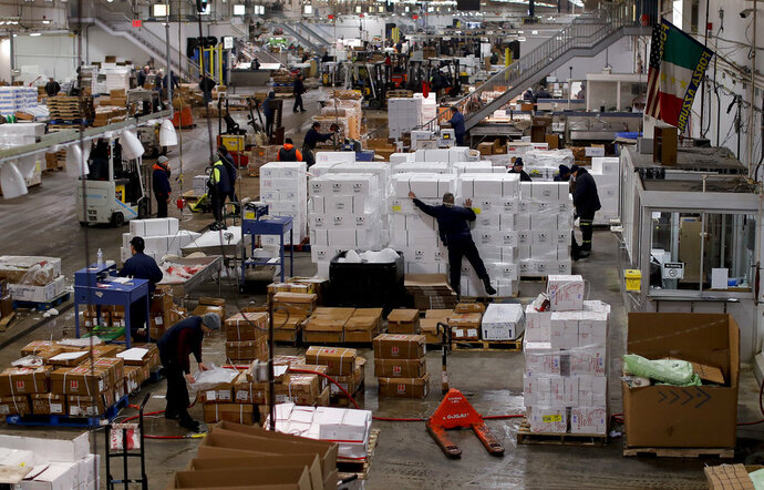 Fishmongers prepare orders for buyers at the New Fulton Fish Market in New York on Monday, Jan. 8, 2018. The nine-acre refrigerated warehouse just outside Manhattan is the second-largest facility of its kind worldwide, moving millions of pounds of seafood each night, much of it flown in fresh from across the globe. (AP Photo/Julie Jacobson)