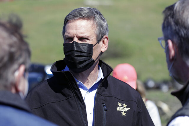 Tennessee Gov. Bill Lee, center, visits a storm-damaged area Tuesday, April 14, 2020, in Chattanooga, Tenn. Tornadoes went through the area Sunday, April 12. (AP Photo/Mark Humphrey)