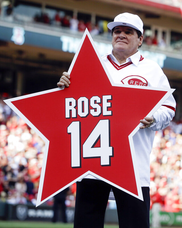 FILE -In this June 24, 2016, file photo, former Cincinnati Reds player Pete Rose (14) holds his place marker during a ceremony to honor the 1976 World Series champion team, before the Reds' baseball game against the San Diego Padres in Cincinnati. Rose once again asked Major League Baseball to end his lifetime ban, saying the penalty is unfair compared with discipline for steroids use and electronic sign stealing. Rose's lawyers submitted the application Wednesday, Feb. 5, 2020, to baseball Commissioner Rob Manfred, who in December 2015 denied the previous request by the career hits leader. (AP Photo/John Minchillo, File)