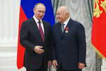FILE - In this Thursday, Sept. 22, 2016 file photo, Russian President Vladimir Putin, left, presents a medal to former Moscow Mayor Yuri Luzhkov during an award ceremony in Moscow's Kremlin, Russia. The former mayor of Moscow and one of the founders of Russia's ruling United Russia party, Yuri Luzhkov, has died at the age of 83. Russia's Ren TV channel reported Tuesday Dec. 10, 2019, that Luzhkov died in Munich, where he was undergoing heart surgery. (AP Photo/Ivan Sekretarev, pool, FIle)