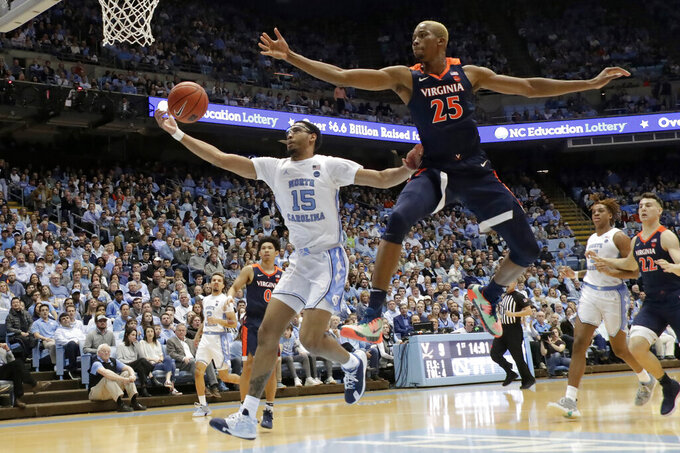 North Carolina's Garrison Brooks (15) and Virginia's Mamadi Diakite (25) go for the ball during the first half of an NCAA college basketball game at the Dean Smith Center in Chapel Hill, N.C., Saturday, Feb. 15, 2020. (AP Photo/Chris Seward)