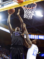 Washington forward Noah Dickerson, left, goes up against UCLA guard Kris Wilkes during the first half of an NCAA college basketball game in Los Angeles, Sunday, Dec. 31, 2017. (AP Photo/Ringo H.W. Chiu)