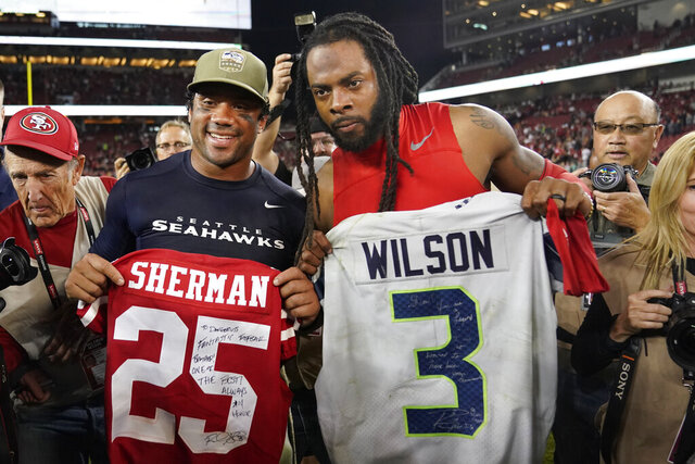 FILE - In this  Monday, Nov. 11, 2019 file photo, Seattle Seahawks quarterback Russell Wilson, left, exchanges jerseys with San Francisco 49ers cornerback Richard Sherman after an NFL football game in Santa Clara, Calif. NFL teams will be prohibited from postgame interactions within 6 feet of each other, so players won't be allowed to exchange jerseys after games as part of the guidelines to help limit the spread of the coronavirus.The restrictions are outlined in the game-day protocols finalized by the league and NFL Players Association on Wednesday, July 8, 2020.  (AP Photo/Tony Avelar, File)