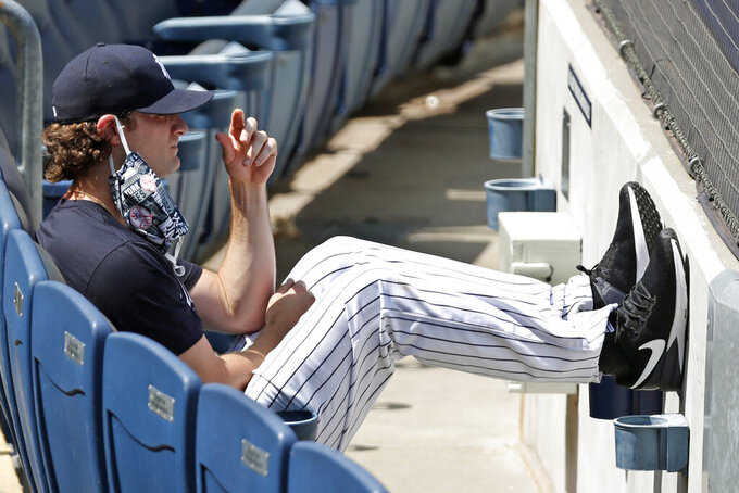 New York Yankees starting pitcher Gerrit Cole watches from the front row of the stands as fellow pitcher James Paxton throws from the mound during a baseball summer training camp workout Sunday, July 5, 2020, at Yankee Stadium in New York. (AP Photo/Kathy Willens)