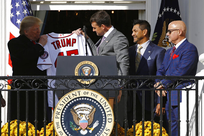 Washington Nationals first baseman Ryan Zimmerman, center, presents a jersey to President Donald Trump during an event to honor the 2019 World Series champion Nationals baseball team at the White House, Monday, Nov. 4, 2019, in Washington. Standing alongside Zimmerman are manager Dave Martinez, second from right, and general manager Mike Rizzo. (AP Photo/Patrick Semansky)