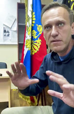In this image taken from video released by Kira Yarmysh on her Twitter account, Russian opposition leader Alexei Navalny gestures as he waits for a court hearing in a police station in Khimki, outside in Moscow, Russia, Monday, Jan. 18, 2021. Russian opposition leader Alexei Navalny's arrest as he arrived in Moscow after recovering from his poisoning with a nerve agent has drawn widespread criticism from Western nations. (@Kira_Yarmysh via AP)