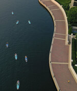 Paddleboarders with stand-up paddleboard company B'More SUP paddle alongside the promenade during a tour of Baltimore's Inner Harbor, Wednesday morning, July 21, 2021. (Jerry Jackson/The Baltimore Sun via AP)
