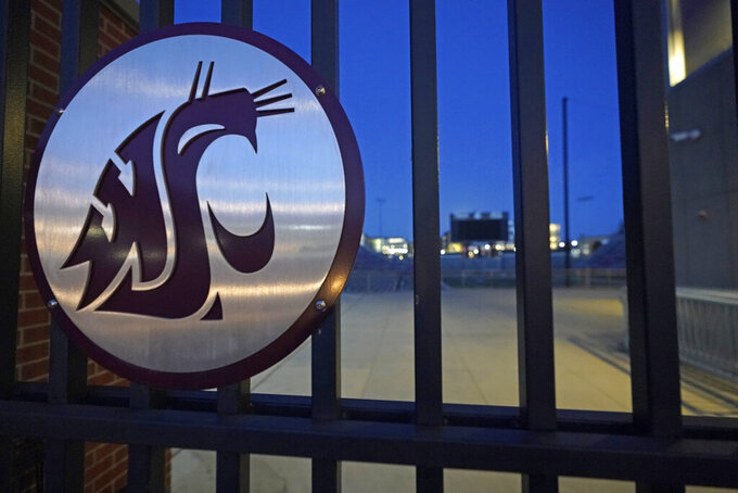 The Washington State Cougar logo is displayed on a gate at Martin Stadium, Monday, Oct. 18, 2021, in Pullman, Wash. Head football coach Nick Rolovich and four of his assistants were fired on Monday for refusing a state mandate that all employees get vaccinated against COVID-19, making him the first major college coach to lose his job over vaccination status. (AP Photo/Ted S. Warren)