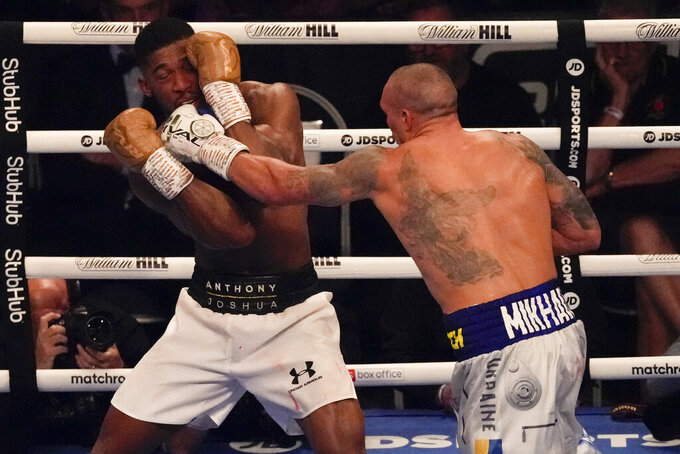 Oleksandr Usyk of Ukraine hits Anthony Joshua of Britain during their WBA (Super), WBO and IBF boxing title bout at the Tottenham Hotspur Stadium in London, Saturday, Sept. 25, 2021. (AP Photo/Frank Augstein)