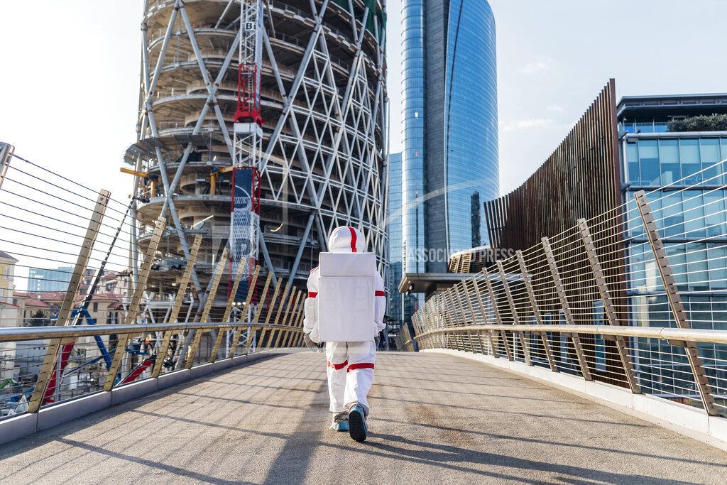 Male astronaut walking on bridge in city