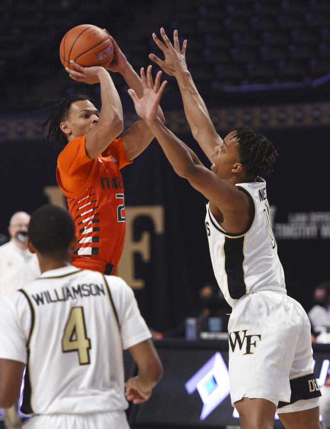 CORRECTS ID TO MIAMI'S ISAIAH WONG, NOT MIAMI'S DONALD CHANEY JR. - Miami's Isaiah Wong, left, sinks a basket under pressure from Wake Forest's Jahcobi Neath during an NCAA college basketball game, Saturday, Jan. 30, 2021, at Joel Coliseum in Winston-Salem, N.C. (Walt Unks/The Winston-Salem Journal via AP)